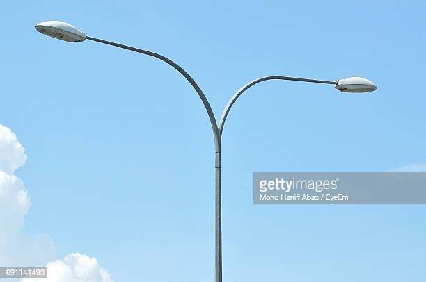 low angle view of street lights against blue sky - street light stock pictures, royalty-free photos & images