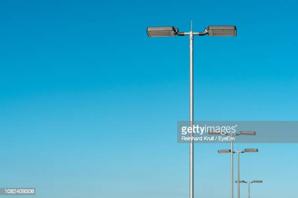 low angle view of street lights against clear blue sky - pole stock pictures, royalty-free photos & images