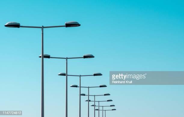 low angle view of street lights against clear blue sky - poste imagens e fotografias de stock