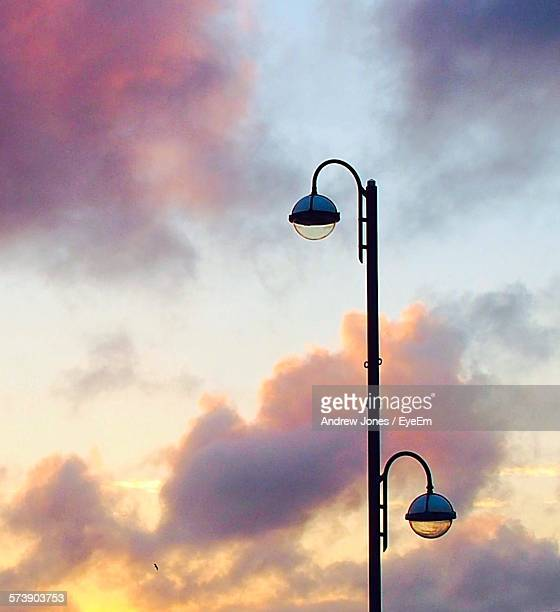 Low Angle View Of Street Lights Against Cloudy Sky At Sunset