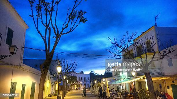 low angle view of street lights amidst houses at dusk - insel ibiza stock-fotos und bilder