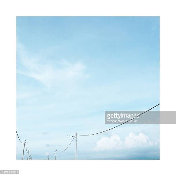 low angle view of street lights and cables against sky - transfer image stock pictures, royalty-free photos & images