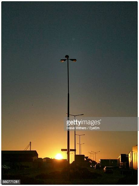 low angle view of street lights in row at sunset - invercargill stock pictures, royalty-free photos & images