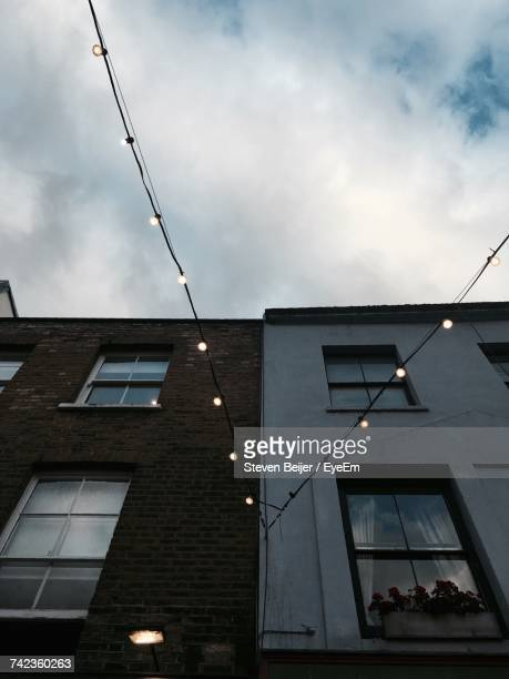 Low Angle View Of String Lights Hanging By Buildings Against Cloudy Sky