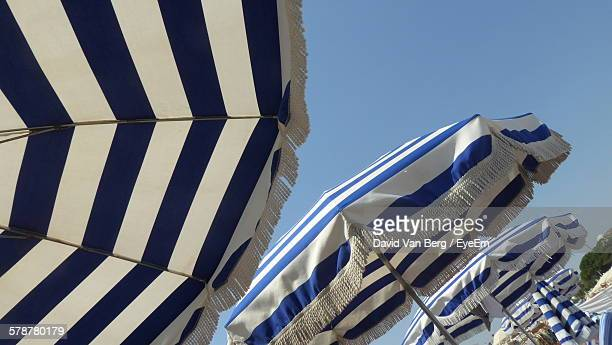 Low Angle View Of Striped Beach Umbrellas Against Clear Sky