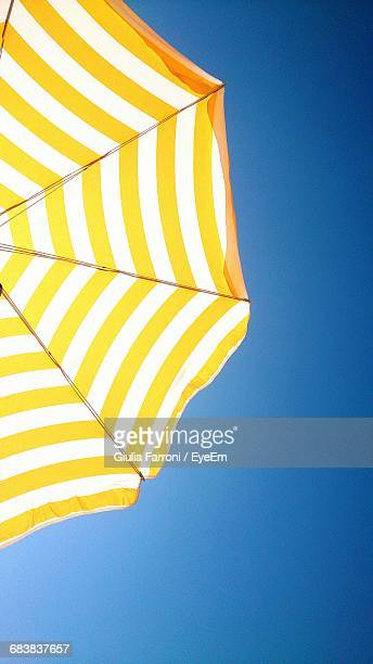 low angle view of striped yellow parasol against clear blue sky - sombrilla de playa fotografías e imágenes de stock