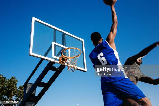 low angle view of strong basketball player with ball in one hand aiming to score - black photos et images de collection