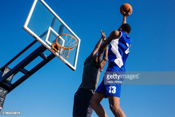 Low angle view of strong basketball players trying to score and defend
