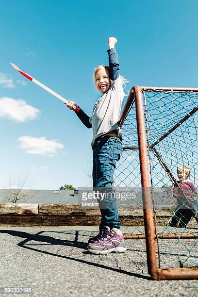 Low angle view of successful girl holding hockey stick against blue sky