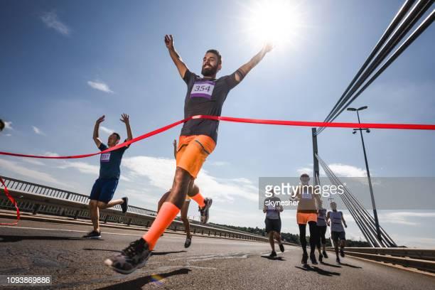 niedrigen winkel ansicht des erfolgreichen menschen überqueren der ziellinie auf marathon-rennen. - ziellinie stock-fotos und bilder