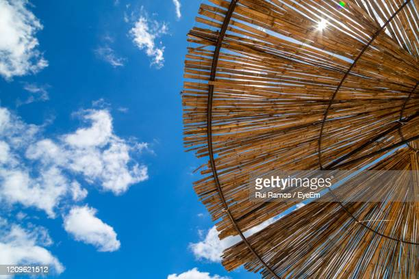 low angle view of sun shade   against blue sky - parasol stock pictures, royalty-free photos & images
