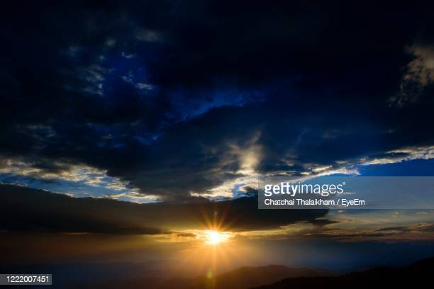 low angle view of sunlight streaming through clouds during sunset - chatchai thalaikham stock pictures, royalty-free photos & images