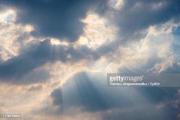low angle view of sunlight streaming through clouds - paradise stock pictures, royalty-free photos & images