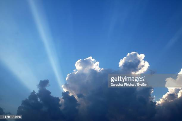 low angle view of sunlight streaming through clouds - earth angel stock pictures, royalty-free photos & images