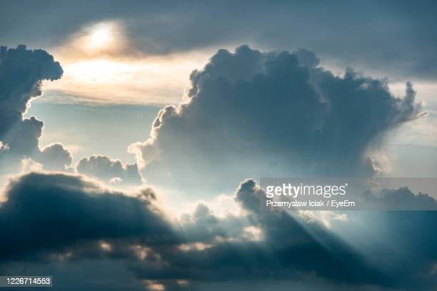 low angle view of sunlight streaming through clouds - cloudscape stock pictures, royalty-free photos & images