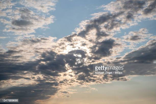 low angle view of sunlight streaming through clouds,nieby,germany - norbert zingel stock-fotos und bilder