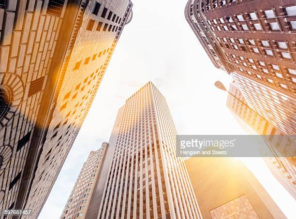 Low angle view of sunlit office skyscrapers, Manhattan financial district, New York, USA