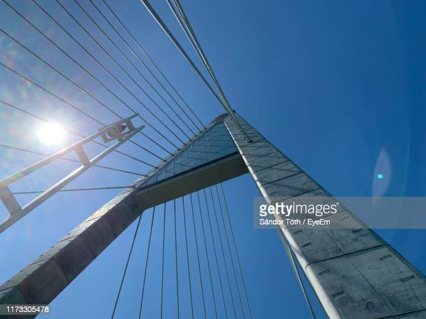 low angle view of suspension bridge against clear blue sky - suspension bridge stock photos and pictures