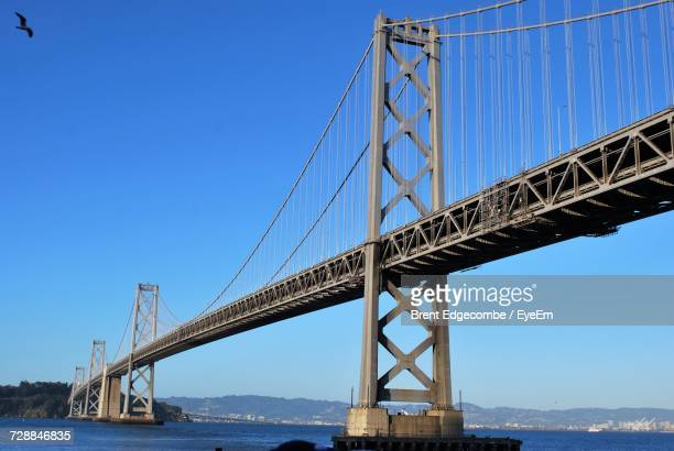 low angle view of suspension bridge against clear blue sky - bay bridge stock pictures, royalty-free photos & images