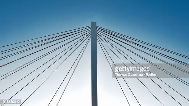 low angle view of suspension bridge against clear blue sky - suspension bridge stock pictures, royalty-free photos & images