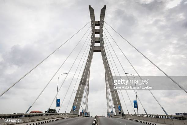 low angle view of suspension bridge against cloudy sky - nigeria stock pictures, royalty-free photos & images