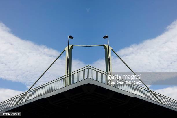 low angle view of suspension bridge against cloudy sky - klaus-dieter thill stock-fotos und bilder