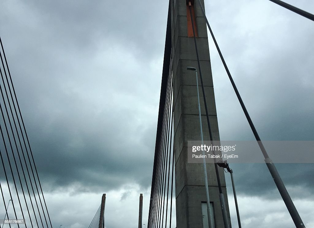 Low Angle View Of Suspension Bridge Against Cloudy Sky : Stockfoto