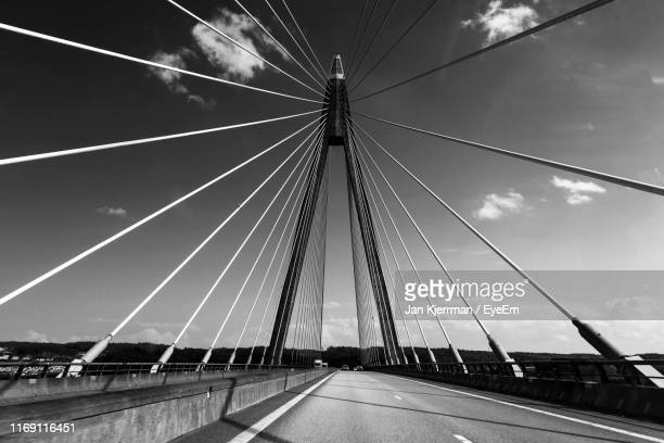 low angle view of suspension bridge against sky in city - sweden stock pictures, royalty-free photos & images