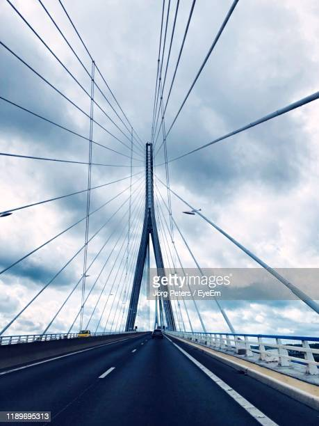 "low angle view of suspension bridge against sky - ""jörg peters"" stock-fotos und bilder"