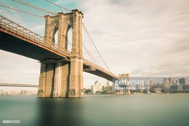 low angle view of suspension bridge against sky - brooklyn bridge stock pictures, royalty-free photos & images