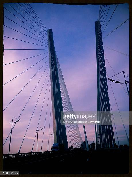 Low angle view of suspension bridge cables against the sky