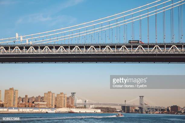 Low Angle View Of Suspension Bridge Over River In City