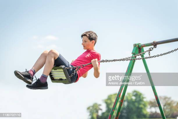 low angle view of swinging on swing against sky - northampton stock pictures, royalty-free photos & images