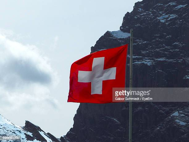 Low Angle View Of Swiss Flag Against Rocky Mountain