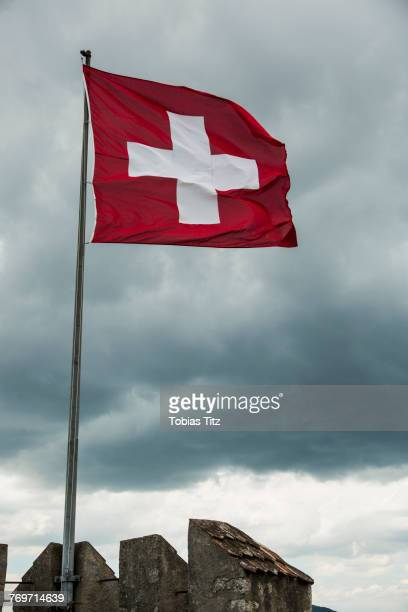 Low angle view of Swiss Flag flapping in wind against cloudy sky