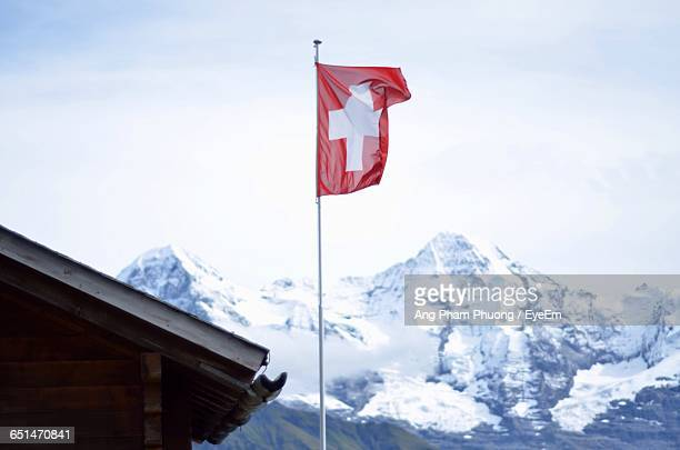 Low Angle View Of Swiss Flag Waving Against Snowcapped Mountains