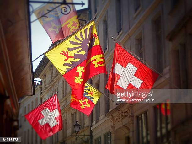 Low Angle View Of Swiss Flags Amidst Buildings