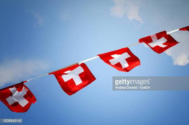 low angle view of swiss flags hanging against sky - drapeau suisse photos et images de collection