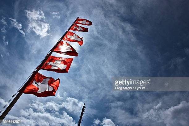 Low Angle View Of Swiss Flags On Mast Against Sky