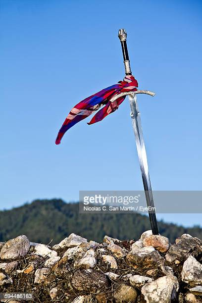 low angle view of sword on stone wall against sky - sword in the stone stock photos and pictures
