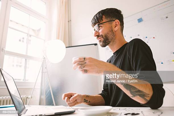 low angle view of tattooed young man working at desk in office - hipster culture stock pictures, royalty-free photos & images