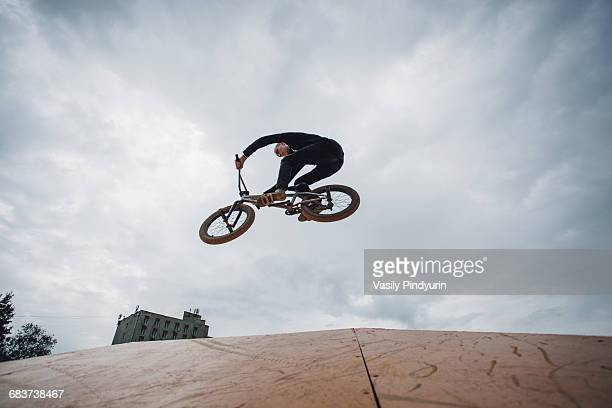 Low angle view of teenager performing stunt during BMX cycling against cloudy sky