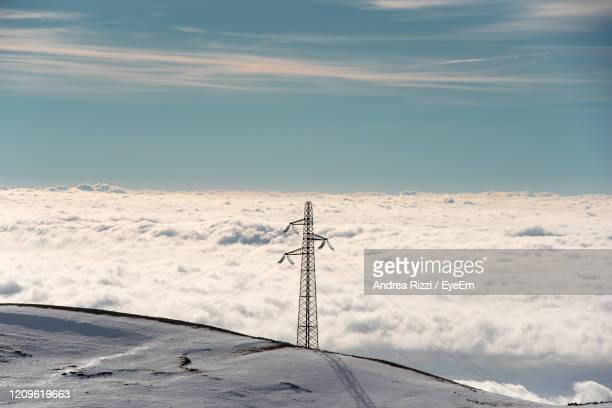 low angle view of telephone pole against sky during winter - andrea rizzi foto e immagini stock