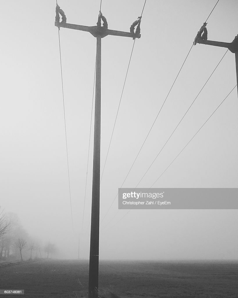 Low Angle View Of Telephone Poles On Field During Foggy Weather : Stock Photo