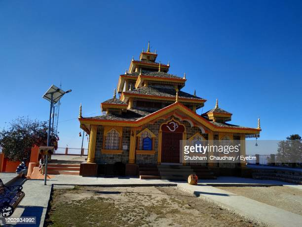 low angle view of temple against building against clear blue sky - reality kings stock pictures, royalty-free photos & images