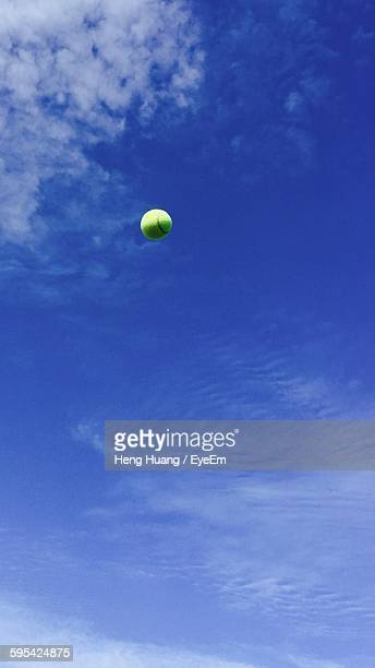low angle view of tennis ball in mid-air against sky - テニスボール ストックフォトと画像