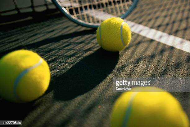 low angle view of tennis balls and a racket on a tennis court