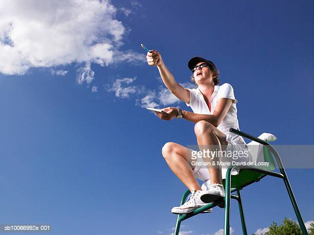 low angle view of tennis umpire sitting in chair, pointing - referee stock pictures, royalty-free photos & images