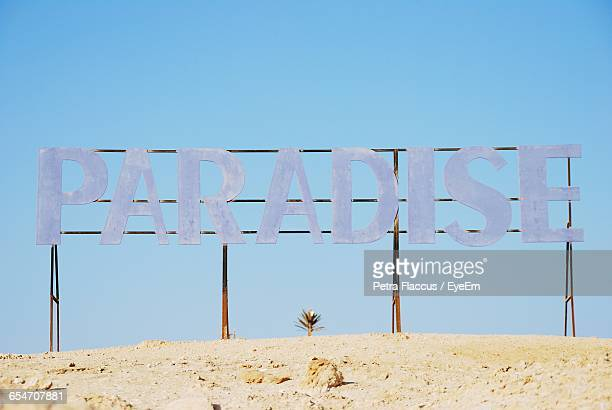 Low Angle View Of Text At Beach Against Clear Sky
