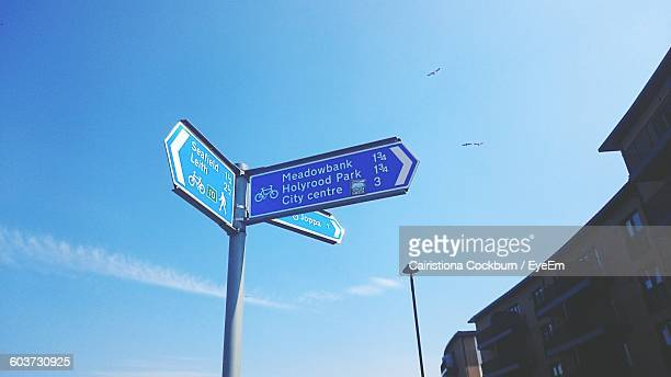 Low Angle View Of Text On Directional Sign Against Sky